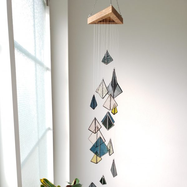 stained glass mobile in pink, blue, grey, and yellow