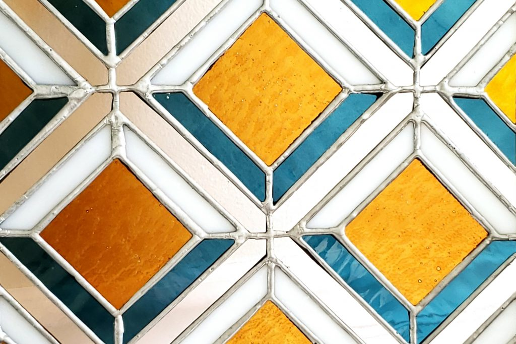 Close Up of Orange Blue and Pink Diamond Pattern Stained Glass