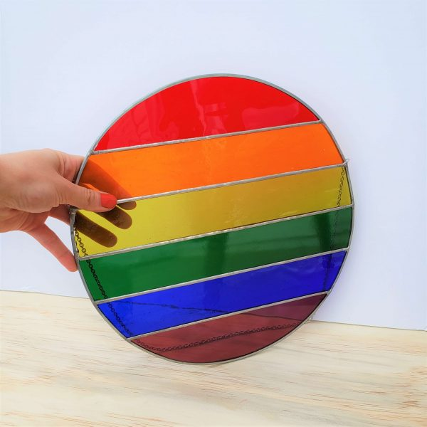 A large circular stained glass pride flag held with one hand