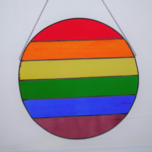 A large round stained glass pride flag suncatcher